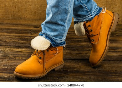 female feet in winter boots and jeans  on wooden background