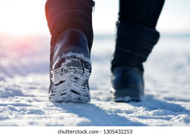 Female feet in winter boots, walking in the snow.