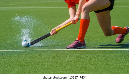 Female field hockey player passing to a team mate on a modern, water artificial astroturf field