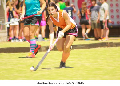 Female field hockey player running with the ball during match. Front view