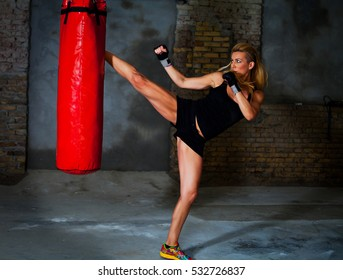 Female fighter kicks a boxing bag with a high leg kick