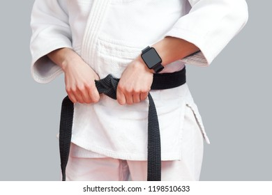Female fighter torso poses in white kimono, smartwatch and sportive strong arms are closeup black belt. sport and technology healthcare concept. Indoor studio shot, isolated on grey background