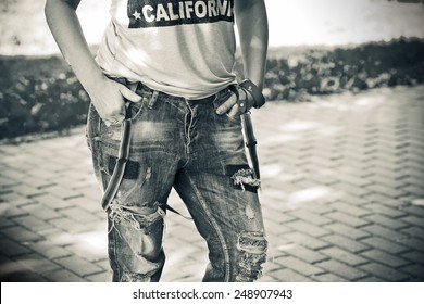 Female figure close-up: ripped jeans worn with suspenders, shirt, a bracelet on her arm. Discolored Photo