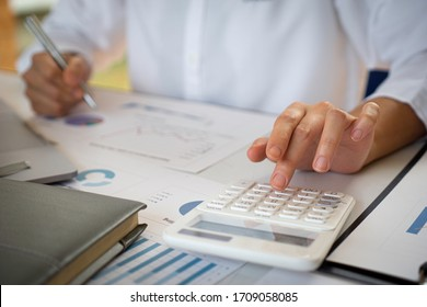 The female finance staff is calculating the company's profits from the graph on the home office desk. Concept finance