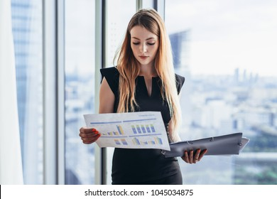 Female financial analyst holding papers studying documents standing against window with city view