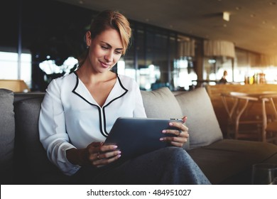 Female financier is reading financial news in internet via touch pad during work break in modern cafe. Confident woman lawyer is using digital table, while is waiting client in an informal setting
