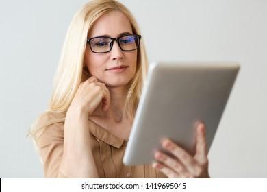 Female Financier Reading News On Tablet Online, Having Break In Office