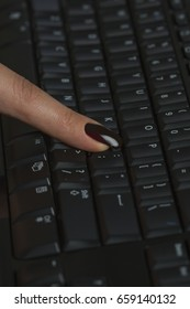 Female finger against the keyboard
