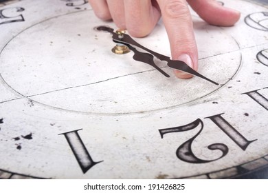 Female finger changes the time on a clock over white