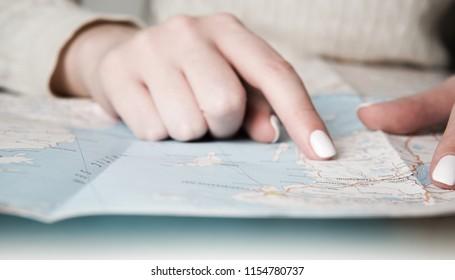 Female finger on map