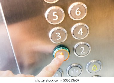 Female finger presses the button on the first floor in an elevator