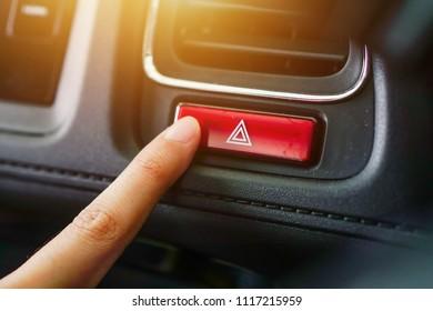 Female finger pressing emergency button on car dashboard in vintage color ,selective focus.