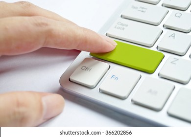 female finger pressing a green button on computer keyboard