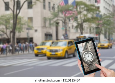 Female finger touching tablet with historic clock in the touchscreen. Intentionally blurred image of a Fifth Avenue (NYC) is in the background. All potential trademarks are removed.