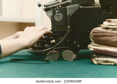 90636dcaf97 Female fingers on the keys of an old typewriter. Near archival documents  and rimless eyeglasses