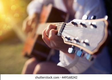 Female fingers playing guitar outdoor in summer park