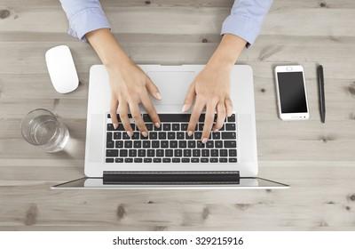 Weibliche Finger tippen auf einer Tastatur an einem Schreibtisch, kein Gesicht