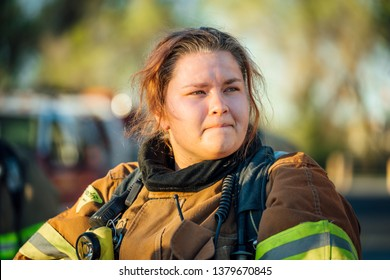 Female firefighter isolated in full bunker gear after a fire.