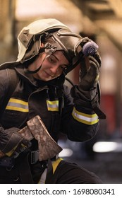 female firefighter portrait wearing full equipment and emergency rescue equipment. taking off oxygen mask after successful intervention. smoke and fire trucks in the background.