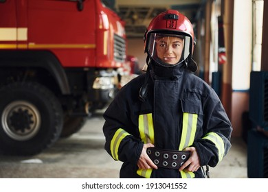 Female firefighter in protective uniform standing near truck.