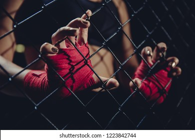 Female fist in bandages for boxing grabs ring grille. Concept of loneliness, struggle, society indifferent.