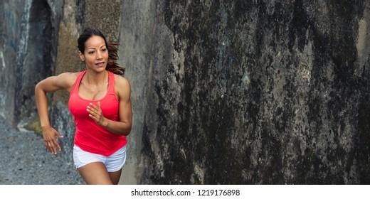 Female fit hispanic athlete running outdoor. Sporty fitness beautiful woman training.