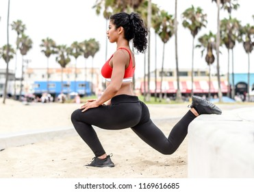 Female fitness athlete at beach park stretches quadriceps  in a lunge position
