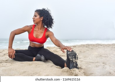 Female fitness athlete stretches on the beach by touching her toes