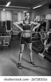 Female fitness. Blonde with a perfect figure, training in the gym. Athletic girl delat exercises with barbell. Strength training.