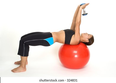 A female fitness instructor demonstrates the finishing position of the dumbbell pullover