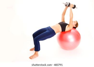 A female fitness instructor demonstrates the finishing position of the dumbbell fly on a fitball