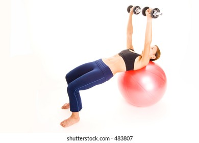 A female fitness instructor demonstrates the finishing position of the dumbell press on a fitball