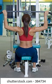 A female fitness instructor demonstrates a lat pulldown