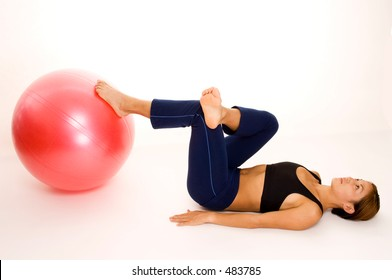 A female fitness instructor demonstrates a one-legged bridge pose