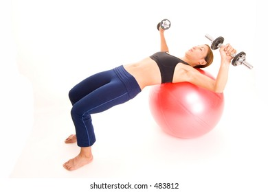 A female fitness instructor demonstrates the starting position of the fitball dumbell press