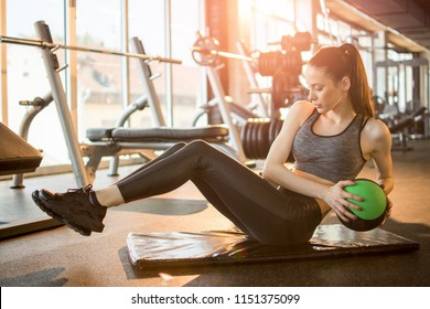Female fitness model exercising with medicine ball at gym.