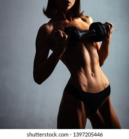 Female fitness model. Fit girl in the gym. Slim young beautiful girl warming up with weights