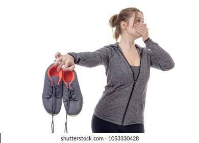 female fitness model holding up her smelly trainers
