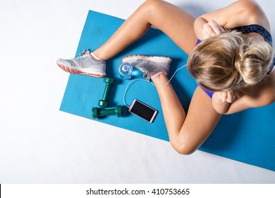Female fitness model resting after an intense workout and taking some a selfie in the mirror of the gym.