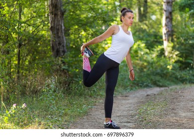 Female fitness model stretching in the forest