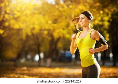 Female fitness model training outside on a warm fall day and listening to music. Sport lifestyle.