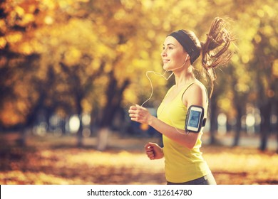 Female fitness model training outside on a warm fall day and listening to music using smart phone. Young woman jogging in autumn park. Sport lifestyle.