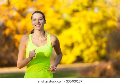 Female fitness model training outside and listening to music. Sport and healthy lifestyle