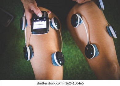 Female fitness model using electronic muscle stimulation technology after a hard training session.