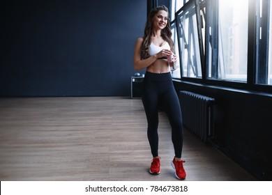 Female fitness model in white top and black leggings is posing near the big windows in studio in morning time