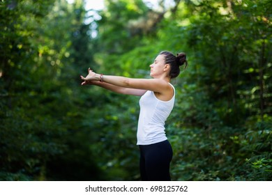 Female fitness model works out in the forest