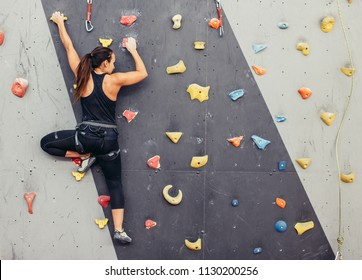 Female fitness professional climber training at bouldering gym. Muscular woman with athletic body dressed in black, climbing on artificial colourful rock wall. Active lifestyle and bouldering concept.