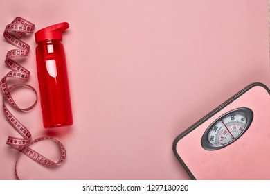Female fitness still life. Scales, measuring tape and bottle for water on pink background. Mockup. Planning of diet and trainings. Top view with copy space. Healthy lifestyle concept. Slimming