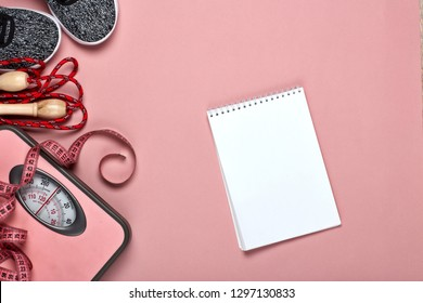 Female fitness still life. Sport accessories, scales and blank sheet of notebook for planning of diet and trainings on pink background. Mockup. Top view. Healthy lifestyle concept