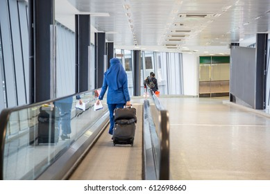 Female flight attendant, a Muslim woman in hijab. Muslim airline. The stewardess walking in the airport